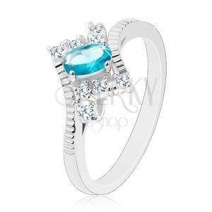 Pierścionek srebrnego koloru, owalna jasnoniebieska cyrkonia, nacięcia na ramionach obraz