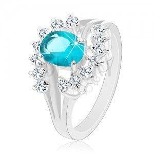 Lśniący pierścionek z rozgałęzionymi ramionami, jasnoniebieski cyrkoniowy owal, przezroczyste łuki obraz