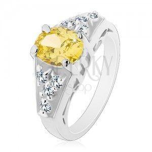 Pierścionek srebrnego koloru, zielono-żółta owalna cyrkonia, kwadraty bezbarwnych cyrkonii obraz